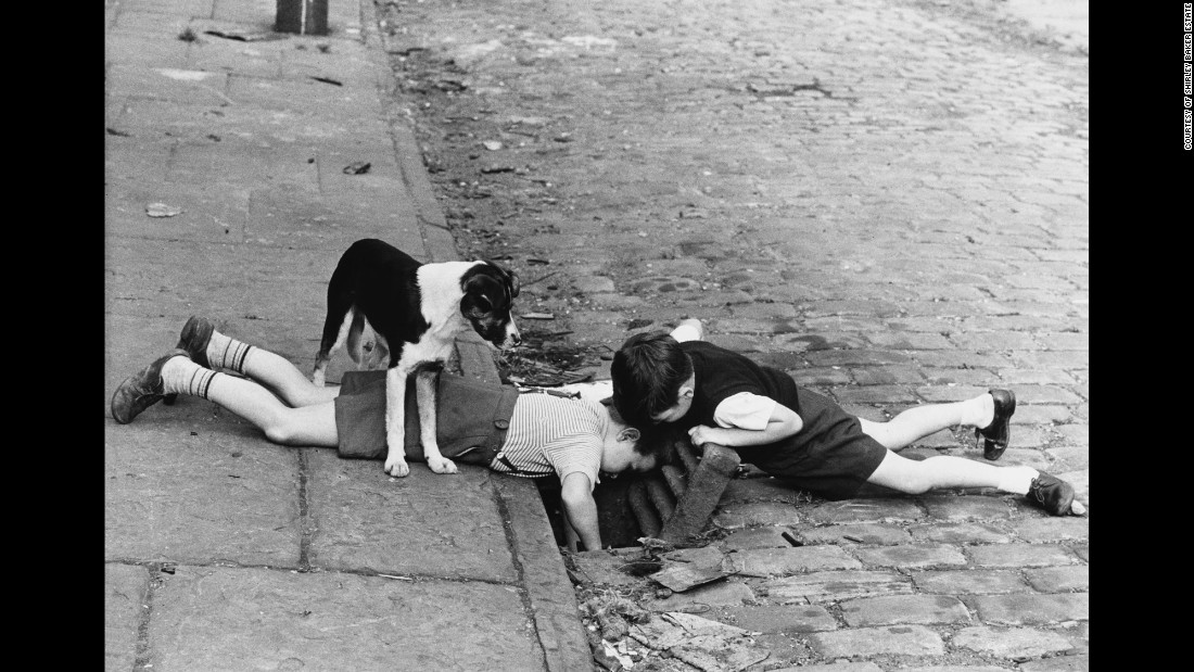 "Two boys, with a faithful dog, search a sewer for something in 1963 Manchester -- a photo that looks like it could come from a 1930s ""Our Gang"" short. ""I didn't intend to go out looking for poverty-stricken areas. What I did find was a great sense of humor,"" Baker wrote for the Tate."