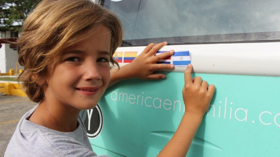 Dimas, 8, affixes the Nicaraguan flag on the back of the bus. The children have been taking turns with the flag stickers, but when they reach the United States, all four plan to put on the Stars and Stripes.
