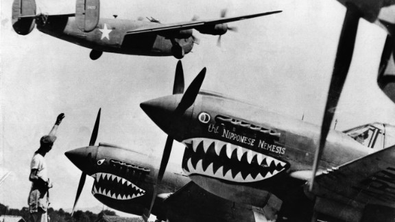 An American soldier waves good luck to a U.S. Army Air Force Liberator bomber as it crosses the shark-nosed bows of U.S. P-40 fighter planes at an advanced U.S. base in China.