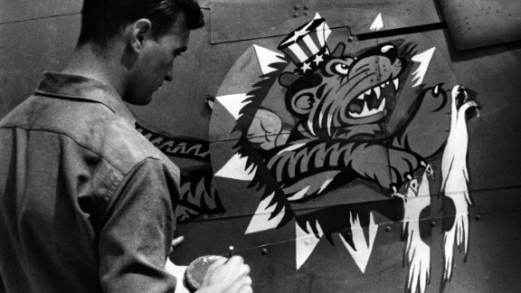 "An artist of the China Air Task Force Fighter Command of the United States Army Air Force puts the finishing touches on the insignia of a U.S. plane. The pilots were known as ""Flying Tigers."""