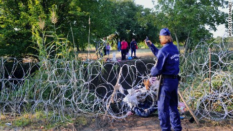 A migrants' group is directed by a Hungarian police official near the Hungarian village of Roszke, at the Hungarian-Serbian border on August 27, 2015. As Hungary scrambles to ramp up defences on its border with Serbia, refugees continued to surge into the country in record numbers, police figures confirmed. AFP PHOTO / ATTILA KISBENEDEKATTILA KISBENEDEK/AFP/Getty Images