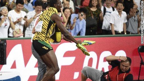 Usain Bolt reacts after a cameraman on a Segway crashes into him in Beijing on Wednesday.