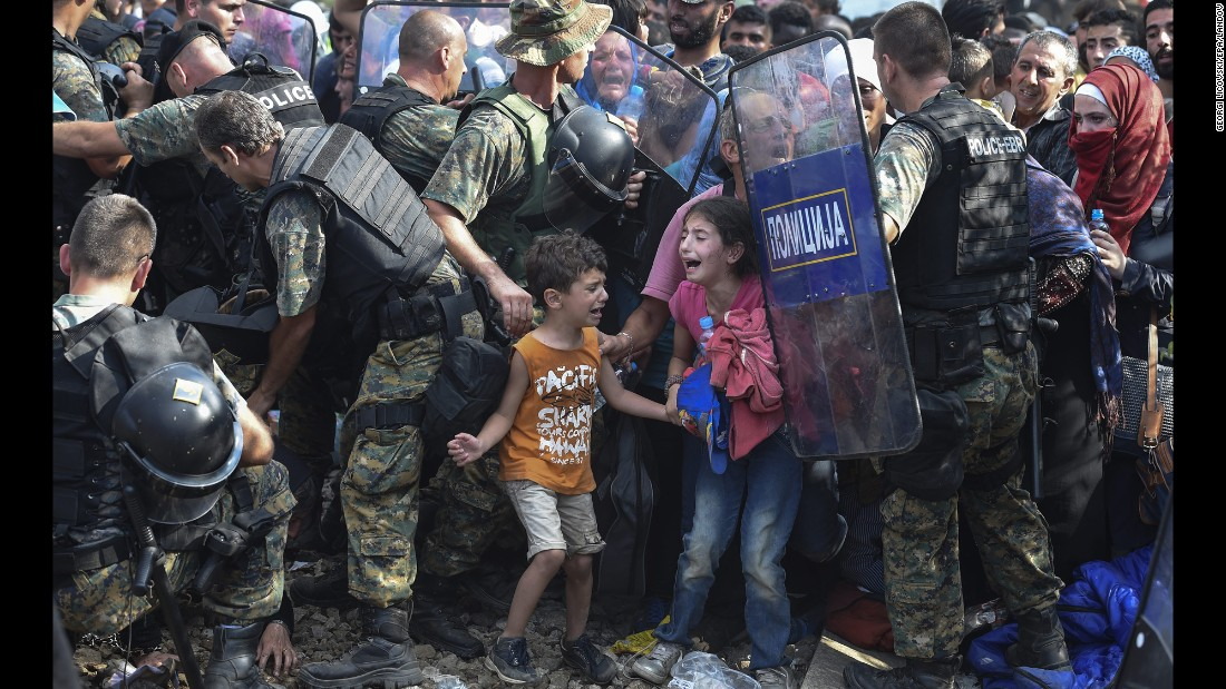 "Children cry as migrants in Greece try to break through police forces to cross into Macedonia on Friday, August 21. Thousands of migrants -- most of them fleeing Syria's bitter conflict -- were stranded in a <a href=""http://www.cnn.com/2015/08/22/europe/europe-macedonia-migrant-crisis/"" target=""_blank"">no-man's land</a> on the border."