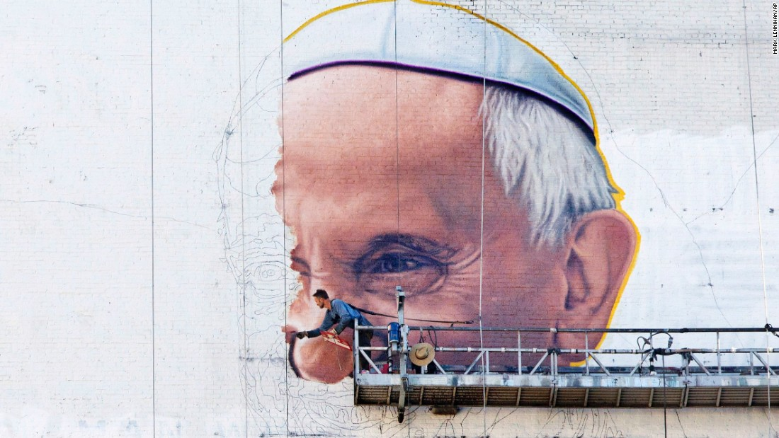 A painter outlines the Pope's nose on the side of a New York City office building on Thursday, August 27. Pope Francis is visiting the United States in September.