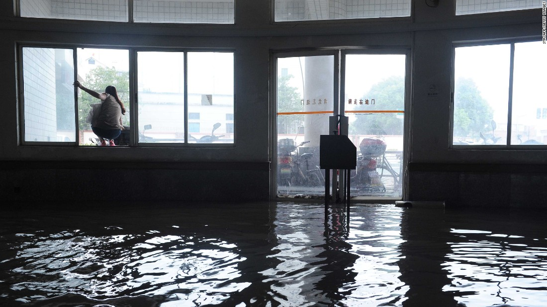 A woman squats in the window of a flooded building after strong rains hit Shanghai, China, on Monday, August 24.