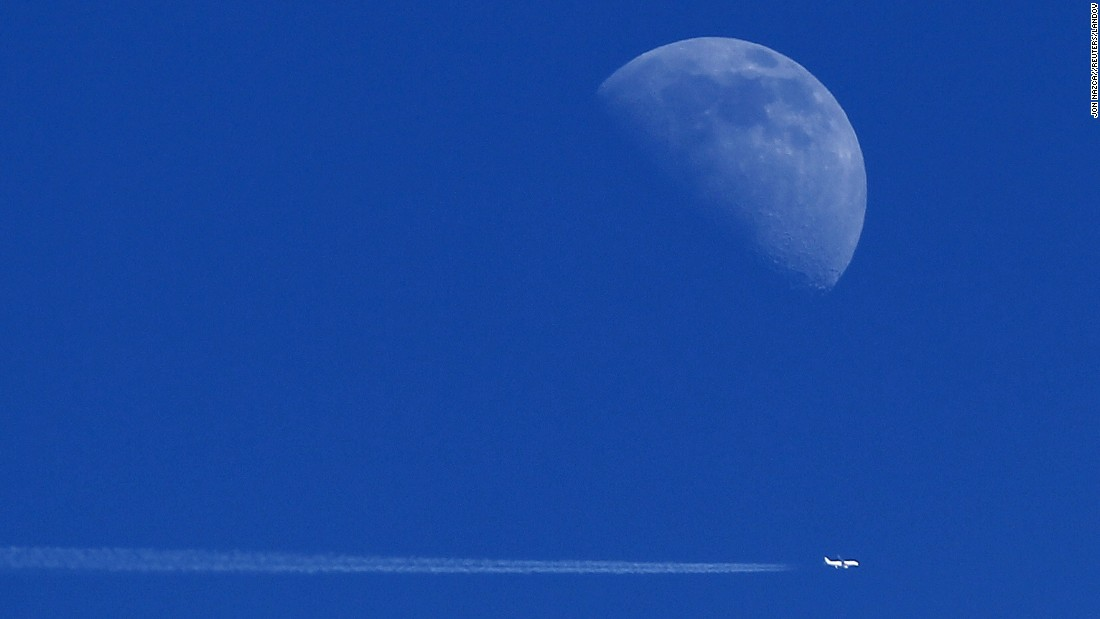 The moon backdrops an airplane flying over Ardales, Spain, on Sunday, August 23.