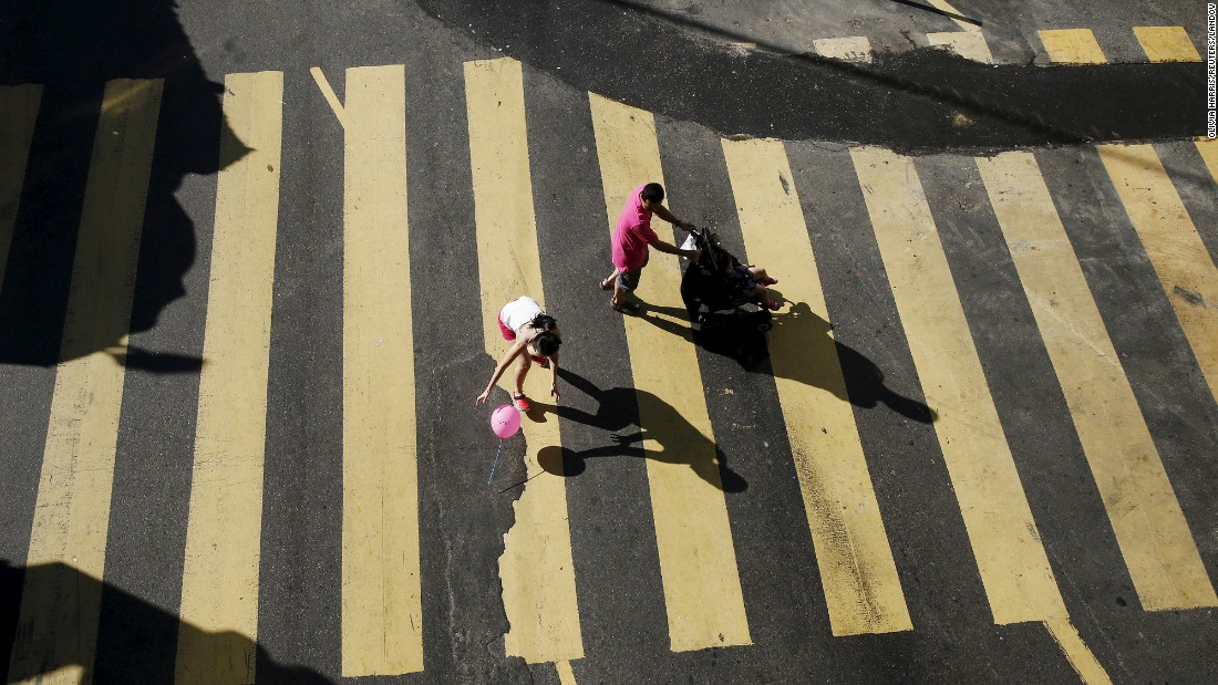 A woman drops a balloon as she crosses a road in Kuala Lumpur, Malaysia, on Friday, August 21.