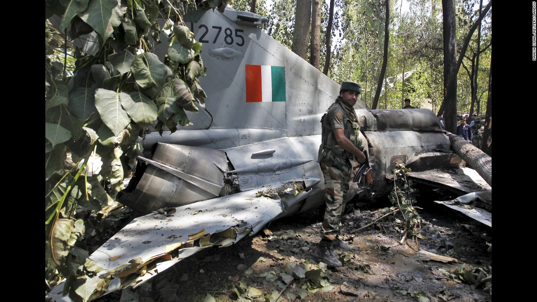 A soldier stands in front of the wreckage of an Indian military aircraft that crashed Monday, August 24, in Soibugh, India. The pilot of the aircraft ejected safely before the crash, according to local media reports.