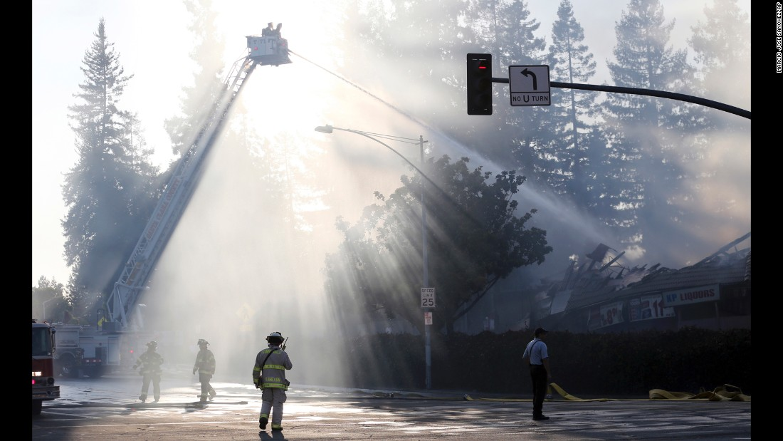 Firefighters battle a blaze in Santa Clara, California, on Wednesday, August 26. The fire was started after a driver struck a gas line, officials said.