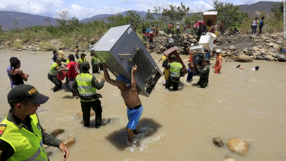 A man from Venezuela carries a refrigerator while crossing the Tachira River border into Colombia on Tuesday, August 25.