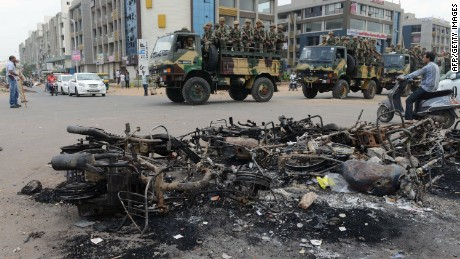 Indian army troops patrol next to the burnt-out remains of vehicles after violent protests in Ahmedabad on August 27, 2015. A court in Gujarat ordered a police inquiry August 27 after at least ten people died in the worst violence to hit the Indian prime minister's home state in more than a decade. AFP PHOTO / Sam PANTHAKYSAM PANTHAKY/AFP/Getty Images