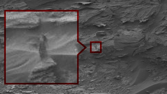 """The Strange Lady: This ghost-like """"woman"""" seems to peering down at Curiosity from a cliff. NASA says it's probably just an oddly shaped drift of sand."""