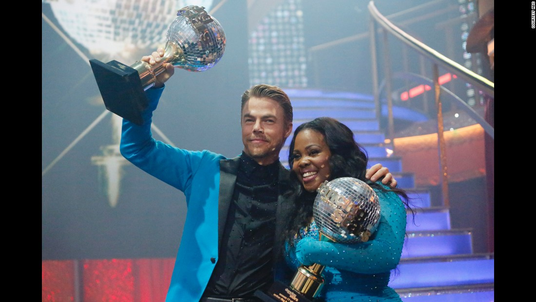 Derek Hough and Amber Riley holding their mirror ball trophies