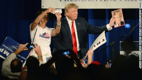 Republican presidential candidate Donald Trump holds a copy of TIME magazine with his likeness of the cover as a woman tries to take a selfie at the National Federation of Republican Assemblies (NFRA) Presidential Preference Convention at Rocketown on August 29, 2015 in Nashville, Tennessee.