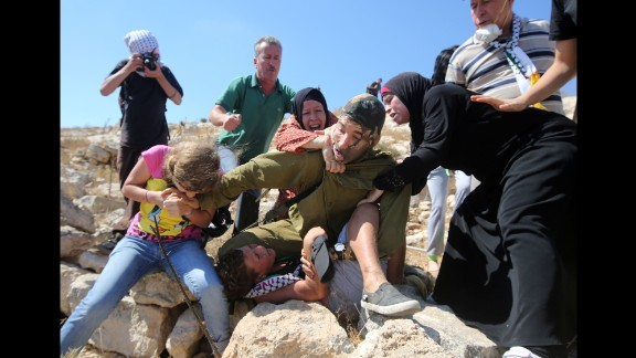 Tamimi, the boy's father, told CNN that his wife and daughter were trying to free his son and clashed with the soldier.