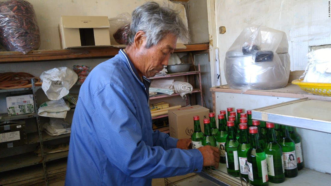 Park Chum-se is pictured handling Soju, a popular Korean liquor, at his store. Business was good a few years back, when soldiers from a nearby base flocked to his store to use phones and buy goods such as cigarettes.