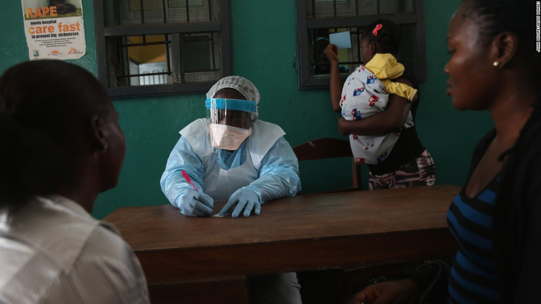 Health workers in protective clothing speak with new arrivals in the outpatient waiting room of Redemption Hospital, formerly an Ebola holding center, in February 2015 in Monrovia, Liberia. The virus has killed at least 3,700 people in Liberia alone, the most of any country, and nearly 9,000 across in West Africa.