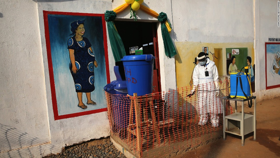 A health worker wearing protective clothing sprays the entrance of Redemption Hospital in Monrovia.