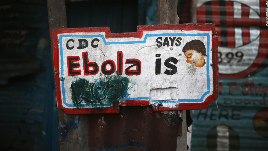 "A sign, originally saying ""Ebola is Real,"" hangs defaced in the West Point township in Monrovia, Liberia, in early 2015. Early in the epidemic, many residents of the seaside slum believed the epidemic was a hoax."