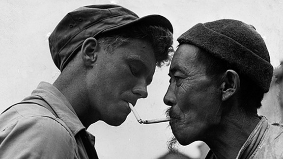 Pausing on a street in bomb-shattered Tengchung, an aged Chinese civilian obtains a light for his cigarette from a U.S. Army sergeant October 14, 1944, who helped drive the Japanese from the ancient city.