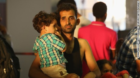 A man from Syria holds one of his children after arriving at the Munich railway station.