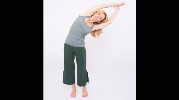 Standing with your arms overhead, take your right wrist in your left hand. Exhale deeply as you side bend to the left. Repeat on the other side, holding the opposite wrist in the opposite hand.