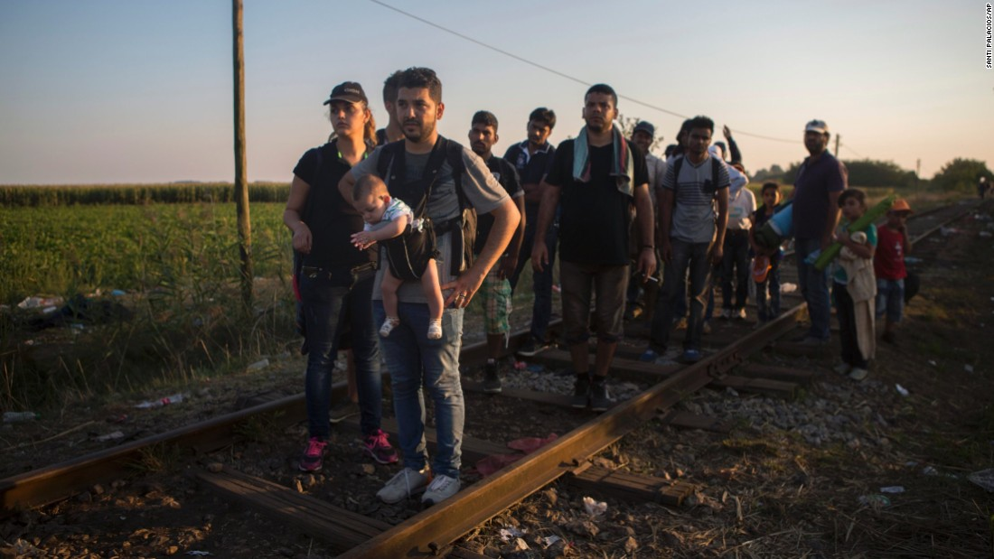 Syrian refugees walk across railways tracks next to the Serbian town of Horgos to cross the border and enter Hungary.