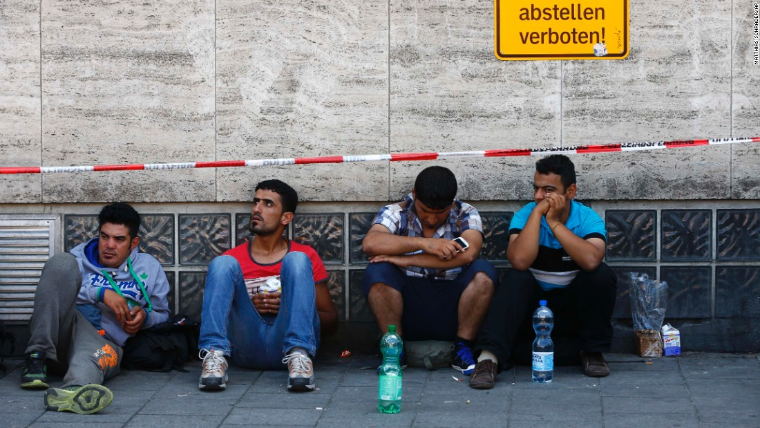 Migrants sit outside the main station in Munich as they wait for their chance to register.