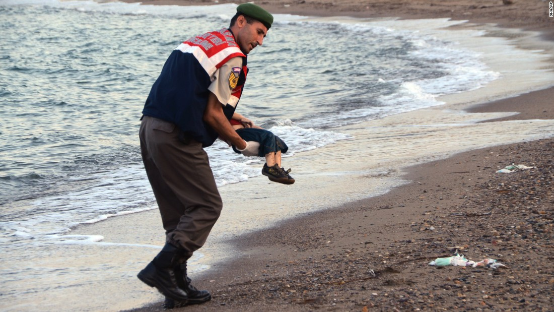 An officer in Bodrum, Turkey, carries Alan's body away from the shore on September 2, 2015.  The child was one of 12 refugees who drowned during a failed attempt to sail to the Greek island of Kos.