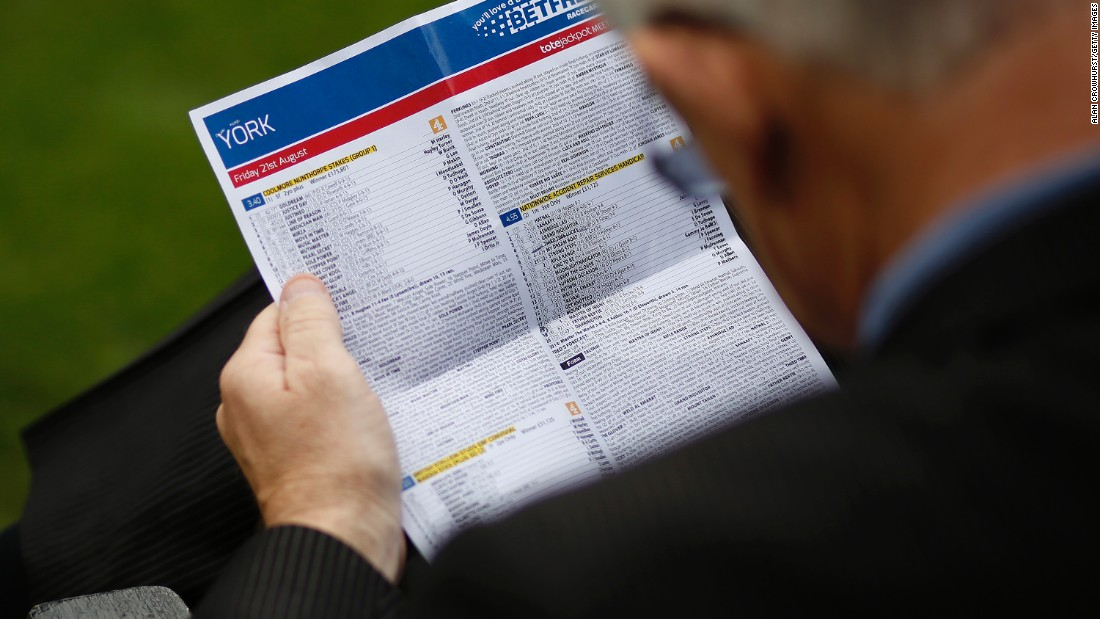 YORK, ENGLAND - AUGUST 21: A racegoer checks the form at York racecourse on August 21, 2015 in York, England. (Photo by Alan Crowhurst/Getty Images)
