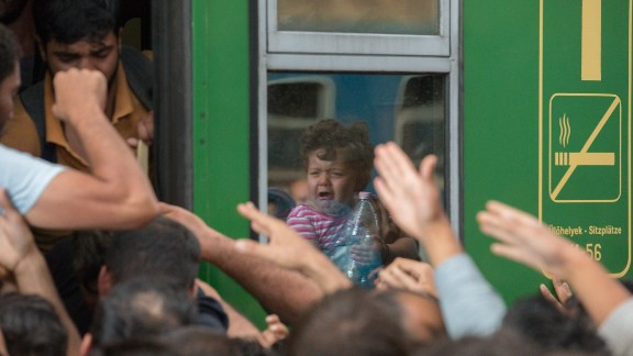 Refugees and migrants board trains in Keleti station after it was reopened in central Budapest.