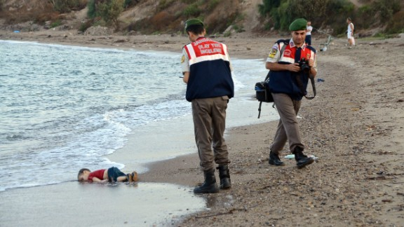 "Authorities stand near the body of 2-year-old Alan Kurdi on the shore of Bodrum, Turkey, in September 2015. Alan, his brother and their mother drowned while fleeing Syria. This photo was shared around the world, often with a Turkish hashtag that means ""Flotsam of Humanity."""