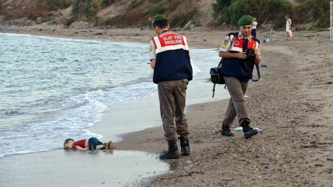 "Authorities stand near the body of 2-year-old Alan Kurdi on the shore of Bodrum, Turkey, in September 2015. Alan, his brother and their mother <a href=""http://www.cnn.com/2015/09/03/europe/migration-crisis-aylan-kurdi-turkey-canada/index.html"" target=""_blank"">drowned while fleeing Syria.</a> This photo was shared around the world, often with a Turkish hashtag that means ""Flotsam of Humanity."""