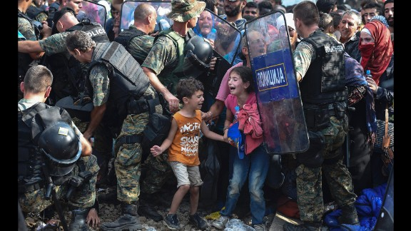 Children cry as migrants in Greece try to break through a police cordon to cross into Macedonia in August 2015. Thousands of migrants -- most of them fleeing Syria's bitter conflict -- were stranded in a no-man's land on the border.
