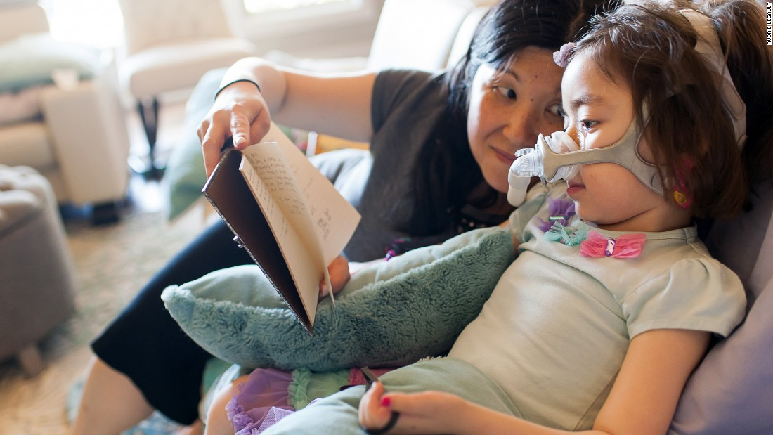 "Michelle reads to Julianna. Her mother has made sure Julianna understands that going to heaven means ""dying and leaving this Earth."" She also told her it meant leaving her family for a while, but they would join her later."