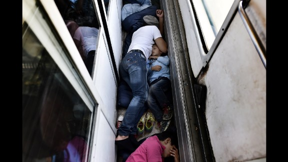 Syrian refugees sleep on the floor of a train car taking them from Macedonia to the Serbian border in August 2015. How to help the ongoing migrant crisis