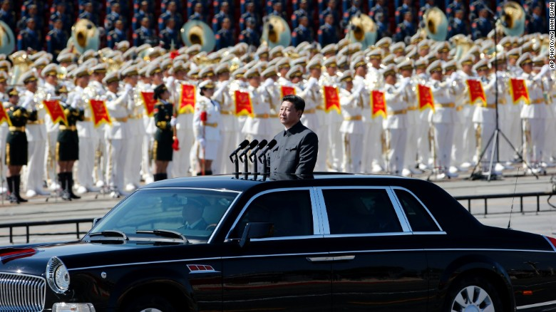 Xi stands in a car to review the army during a parade commemorating the 70th anniversary of Japan's surrender during World War II in Beijing in 2015.