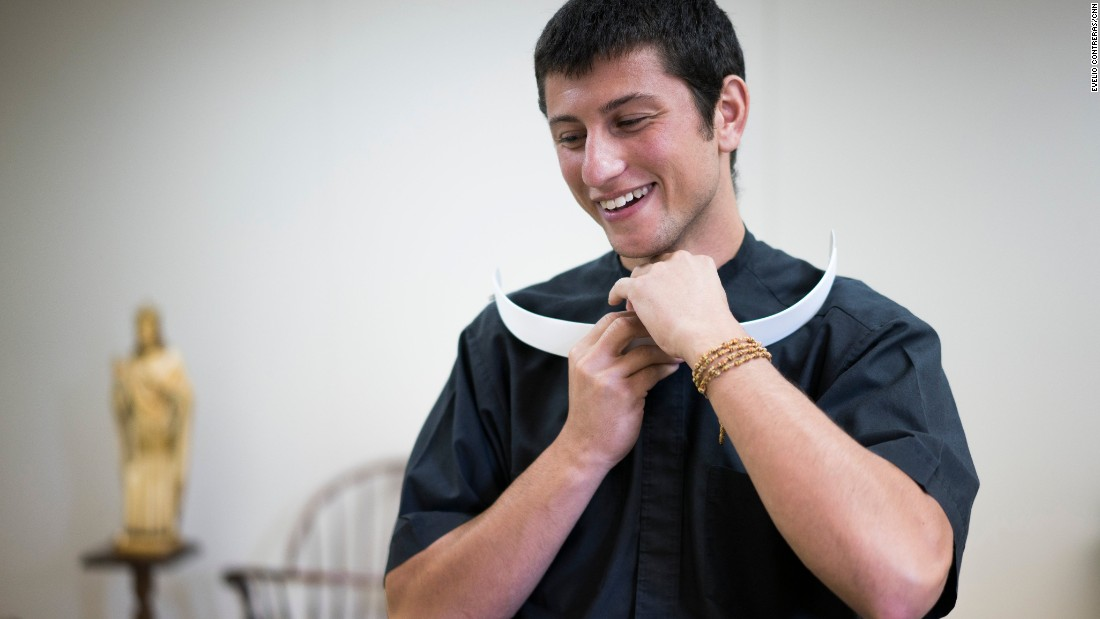 Chris Massaro, a new Catholic seminarian, removes his clerical collar so he can put on his vestments for Mass.