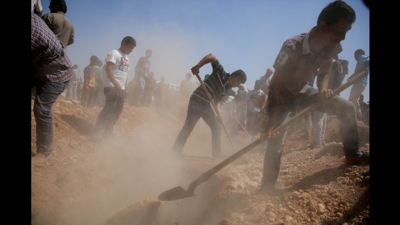Men dig graves for the three coffins in Kobani on September 4, 2015.