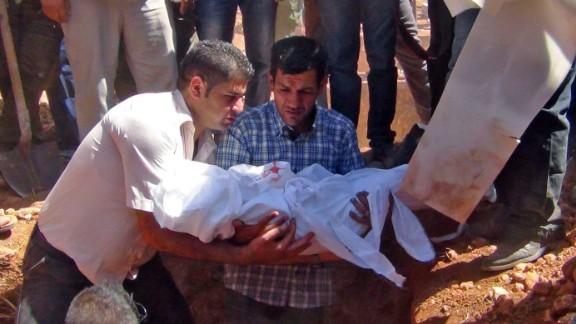Kurdi holds Alan's body before burying him in Kobani on September 4, 2015.