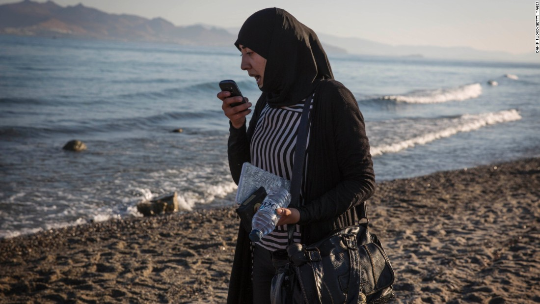 A Syrian woman speaks on the phone while clutching her documents that have been wrapped in plastic to keep them dry during her journey to Kos on August 31.