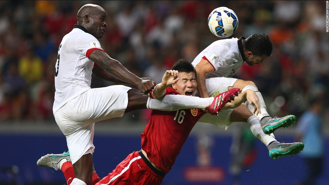 Sun Ke (C) of China tussles for the ball against Jean Jacques Kilama (L) of Hong Kong.