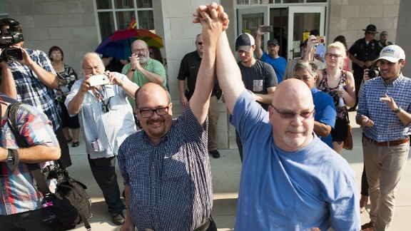 MOREHEAD, KY - SEPTEMBER 04: Michael Long (left) and Timothy Long, of Rowan County, raise their hands in front of a crowd of supporters after receiving their legal marriage license at the Rowan County Courthouse September 3, 2015 in Morehead, Kentucky. Kim Davis, an Apostolic Christian and a Rowan County clerk, refused to issue marriage licenses to same sex couples in defiance of a Supreme Court ruling, citing religious objections. Davis was held in contempt of court and placed in Carter County jail on Thursday, September 3rd. (Photo by Ty Wright/Getty Images)