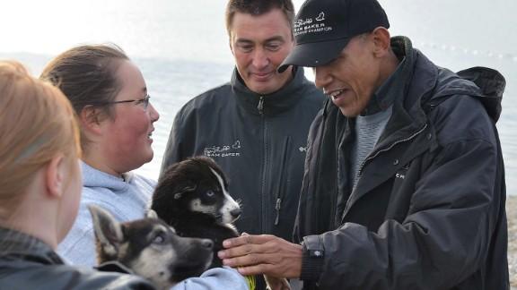 U.S. President Barack Obama says hello to  puppies belonging to musher John Baker (second from the right) in Kotzebue, Alaska, on September 2, 2015.