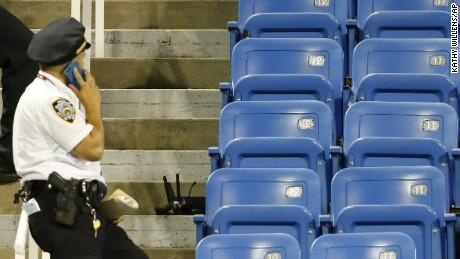 A police officers stands beside the remains of a drone that crashed into an empty section of seats at the U.S. Open tennis tournament in New York.