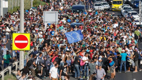 Migrants walk out of Budapest, Hungary, Friday, Sept. 4, 2015. Over 150,000 people seeking to enter Europe have reached Hungary this year, most coming through the southern border with Serbia, and many apply for asylum but quickly try to leave for richer EU countries. (AP Photo/Frank Augstein)