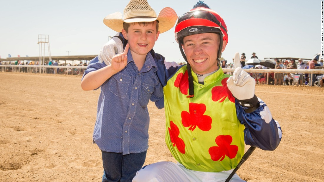 A jockey poses with a young fan before a race.