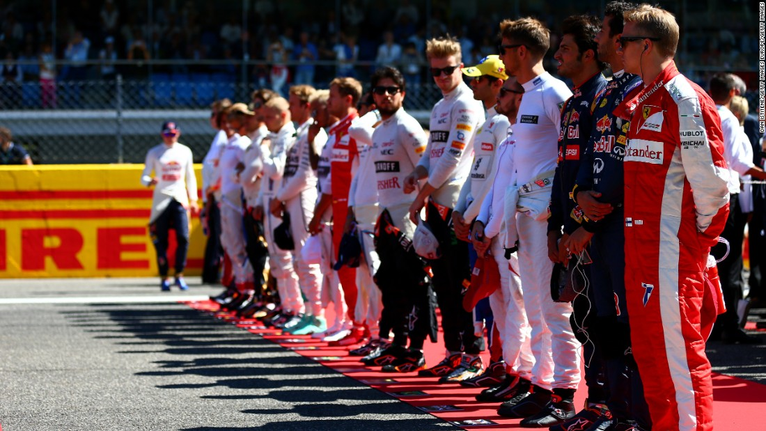 Drivers stand to attention on the grid as the Italian national anthem is played before the action on the track gets under way.