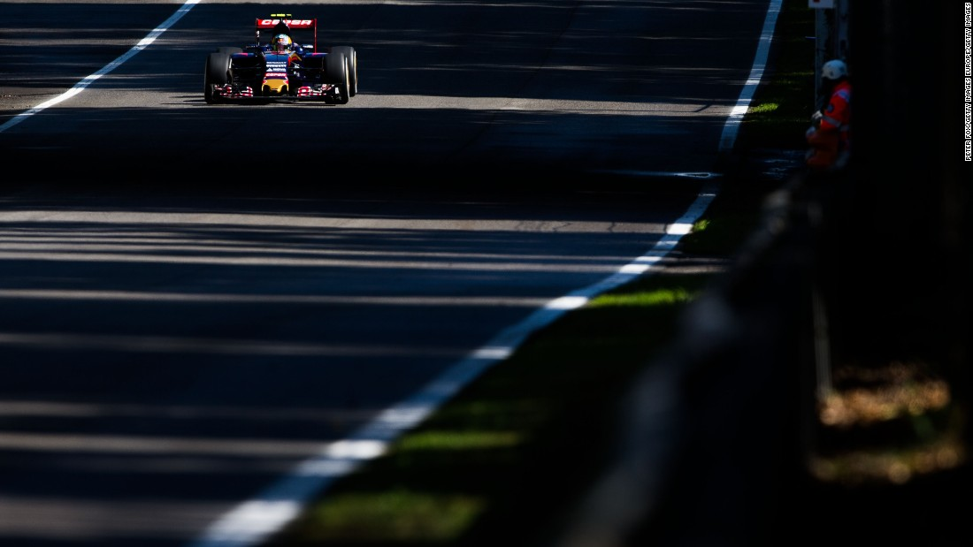 Carlos Sainz's Toro Rosso zips down one of the straights, splintered by sunlight through the trees.