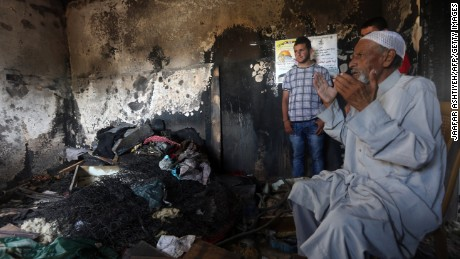 The grandfather of the slain Palestinian boy prays at the family's burned-out home.